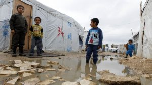 A Syrian refugee boy stands in a pool of water as he looks at others outside tents at a makeshift settlement in Bar Elias in the Bekaa valley January 5, 2015. Lebanon enforced new immigration controls at the Syrian border on Monday in a move to gain control of the steady stream of refugees from its much larger neighbour. REUTERS/Mohamed Azakir (LEBANON - Tags: SOCIETY IMMIGRATION CIVIL UNREST CONFLICT POLITICS)
