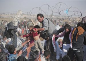 FILE - A Sunday, June 14, 2015 file photo of a Syrian refugee carrying a baby over the broken border fence into Turkey after breaking the border fence and crossing from Syria in Akcakale, Sanliurfa province, southeastern Turkey. The mass displacement of Syrians across the border into Turkey comes as Kurdish fighters and Islamic extremists clashed in nearby city of Tal Abyad. (AP Photo/Lefteris Pitarakis, File)